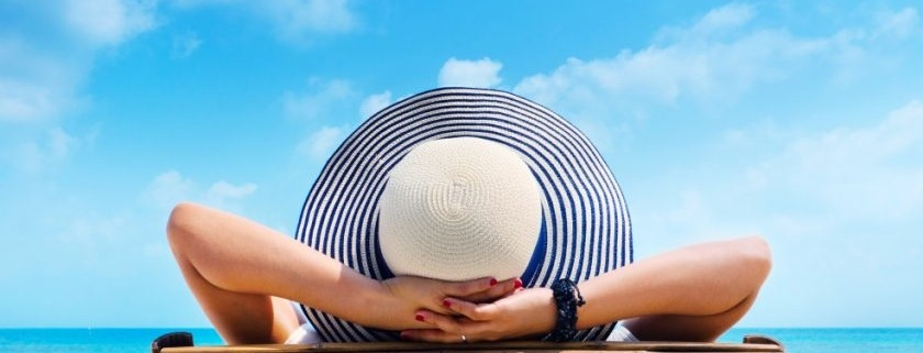 woman in hat relaxing on beach looking at sea t20 NQd1X7 840x487