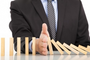 bigstock Businessman Hand Stop Dominoes 57705140 1 e1508698015376